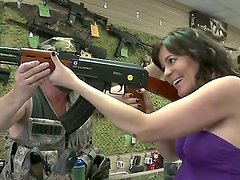 This awesome brunette in her fine and short dress enters the gun shop to buy something for