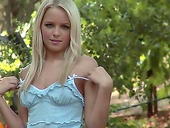 Misty Rhodes the lovely blonde girl poses on camera in the park