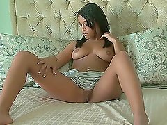 Lauren D'Marie sits on the bed with her legs wide opened