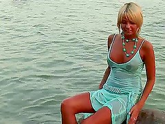 Pretty blonde Masha fingers her pussy on the beach