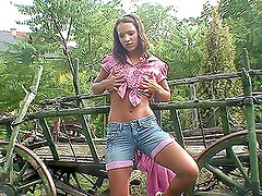 A rural brown-haired chick masturbating her pussy near a carriage
