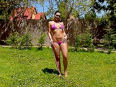 Watch this hot brunette babe playing with a water hose