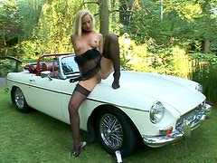 Glamorous blonde bitch Sandy fingers her twat over the shiny car