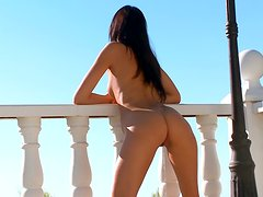 Gorgeous but skinny lady sunbathing on a balcony