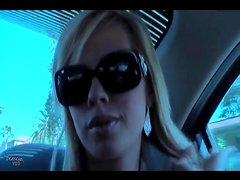 Pretty blonde in sunglasses chats in the car