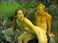 Long-haired brunette gets fucked from behind near a river