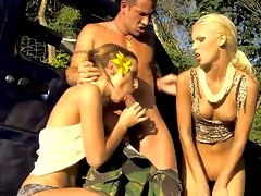 Two girls and one guy fuck outdoors in the field