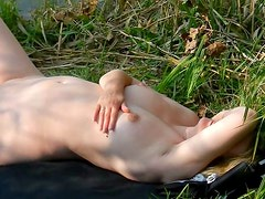 Sunbathing hot blond girl at a lake