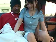 Pigtailed Japanese chick enjoys sucking a black schlong in a car