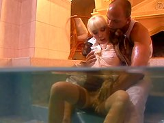 Mature mommy is fucking in a pool being fully dressed
