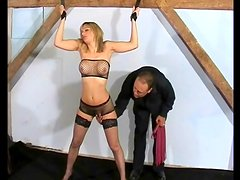 Flogging a fake tits girl in bondage