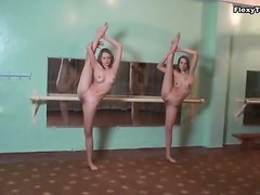 Two flexible ballerinas stretch in gym