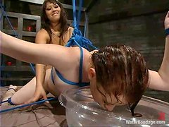 Redhead chick gets toyed with a strap-on by her Asian mistress