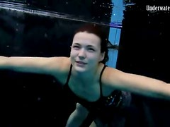 Beautiful girl swims and smiles underwater