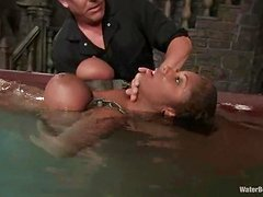 Busty ebony gets her tits cuffed and then gets dipped in the water