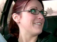 Four eyed red haired girlfriend plays with her pussy in the car