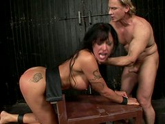 Busty tanned brunette is tied up and gets hammered doggy on wooden table
