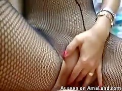 Fantastic slut in fishnets shows pussy