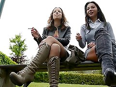2 lesbian sluts smoking on bench in thigh high boots & boobs