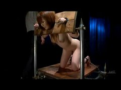 Girl in stockades takes hot wax on ass