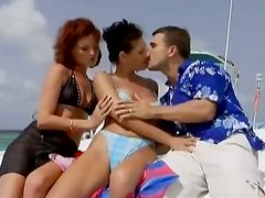 Redhead and brunette chicks get threesomed on a boat