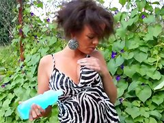 Ebony girl with curly hair gets wet posing on cam by the river