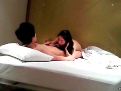 Asian brunette blows her boyfriend in bed