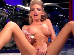 Pornstar with fake tits self stimulates her shaved pussy