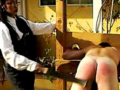Male slave in outdoors bare ass spanking scene