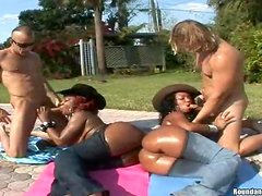 Two big-assed black skanks enjoy outdoor foursome sex