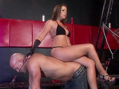 Beauty with a leather whip is playing with her slave