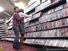 Horny Japanese chick gets clothed sex in a video-store.