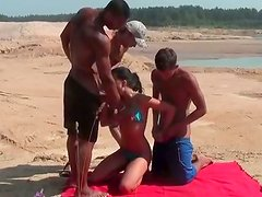 Kinky Russian chick is nailed doggy while sucking meaty cock on a beach
