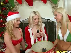 Three blonde babes in Santa costumes share a strapon indoors