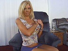 Mature blonde with big fake tits gives a titjob