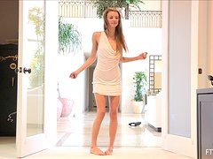 A skinny model takes her dress off and poses naked in a doorway