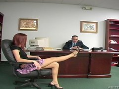 A redhead girl in a miniskirt gives a handjob in an office