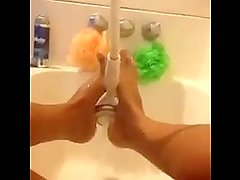 Holding the shower handle with her feet!