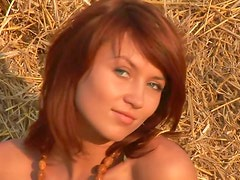 Redhead in the hay at sunset