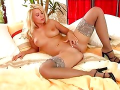 Busty babe in stockings fingers her shaved pussy