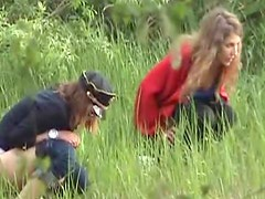 Two girls go pee in a field