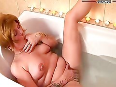 Busty Milf with tattoo and piercing masturbating in tub