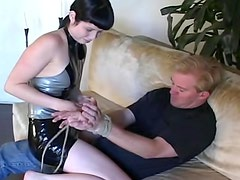 Shiny latex dominatrix abuses him