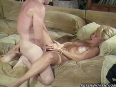 Nina Hartley is having sex with a guy on the couch