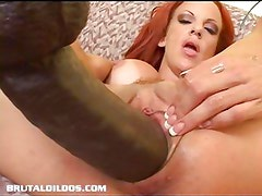 Busty redhead fills her pink pussy with a massive dildo