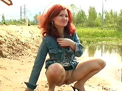 Redhead goes piss in the sand