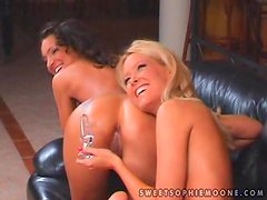 Beautiful lesbians play with a realistic dildo in the living room