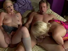 Anita Blue and Raquel Sieb sucking a cock on the bed