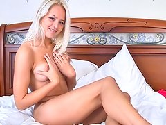 Blonde Jesica Ann lying in her bed with spread legs