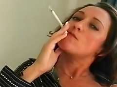 Brunette with sexy face smokes a cigarette with pleasure